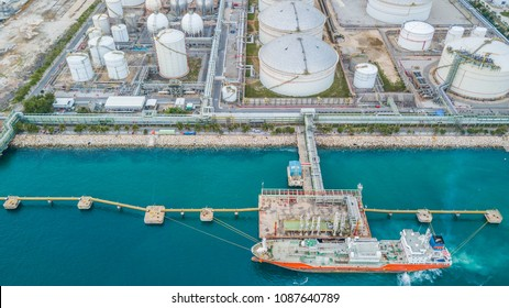 Aerial top view of oil tanker ship at the port, oil terminal is industrial facility for storage of oil and petrochemical products ready for import export business logistic and transportation.