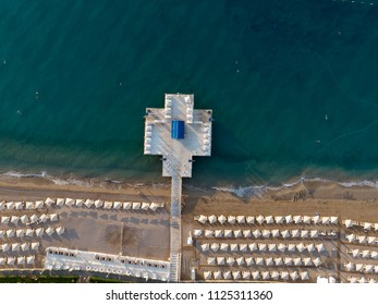 Aerial top view on the beach. Sunbeds, umbrellas, sand and sea waves.