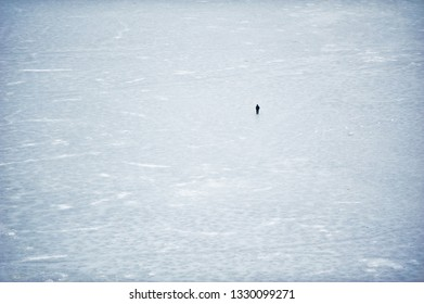 Aerial top view on a frozen lake. Lonely man walking through.