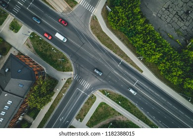 Aerial top view on road in city, junction and city traffic, cars on road, house rooftops