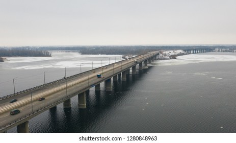 Aerial top view on road bridge across the Dnieper River in Dnipro city at winter time. (Dnepr, Dnepropetrovsk, Dnipropetrovsk). Ukraine.