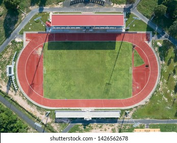 Aerial top view on a soccer field, grandstand, football field with red running track. race track in a stadium.