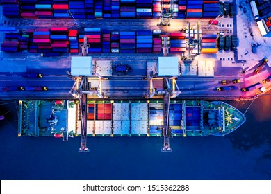 Aerial top view over international cargo ship at industrial import-export port  prepare to load containers with big container loader ship vessel at night. Oversea international Business.