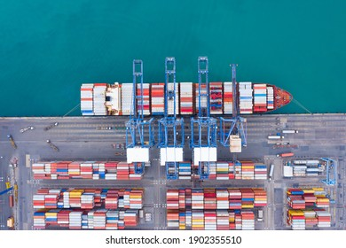 Aerial top view over international containers cargo ship at industrial import-export port prepare to load containers with big container loader ship vessel. global transportation and logistic business.