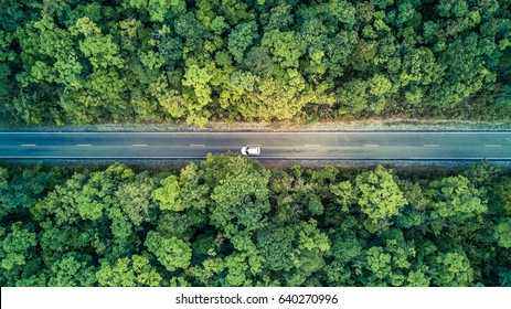 Aerial top view over mountain road going through forest.