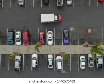 Aerial top view of parking lot at supermarket with with varieties of colored vehicles. People walking to their car and trying to park.