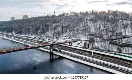 Aerial top view of pedestrian Park bridge in winter and Dnieper river from above, snow Kyiv cityscape, city of Kiev skyline, Ukraine