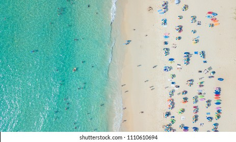 Aerial top view of people crowd relaxing on Phuket beach with umbrellas and turquoise sea, Phuket, Thailand.