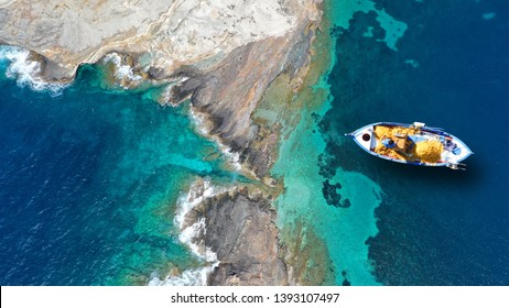 Aerial top view photo of beautiful colourful traditional fishing boat near village of Panormos with turquoise crystal clear sea, island of Tinos , Cyclades, Greece