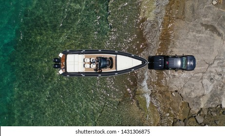 Aerial top view photo of inflatable speed boat on trailer being towed by truck from emerald exotic sea to land