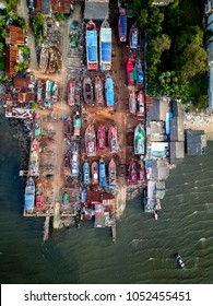 aerial top view photo of local Asian fishing boats in a dry dock of small a small village next to the severely polluted black sea filled with waste water and garbage. Bang Lamung, Chonburi, Thailand.