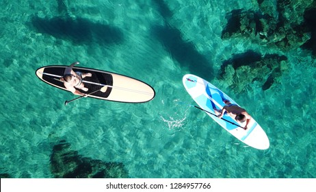 Aerial top view photo of men practising Stand Up Paddle or SUP board in mediterranean clear Aegean island sea