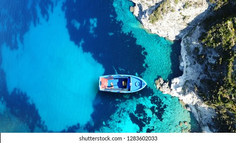 Aerial top view photo of traditional Greek fishing boat docked in famous beach of Tsigrado with turquoise clear sea in picturesque volcanic island of Milos, Cyclades, Greece