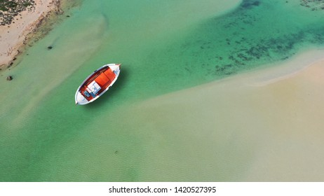 Aerial top view photo of traditional fishing boat in emerald lagoon of iconic Balos, Gramvousa, Crete island, Greece
