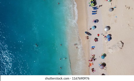 Aerial top view photo of tropical sandy exotic emerald paradise beach with sunbeds and inflatables