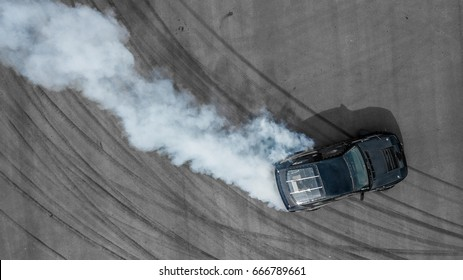 Aerial top view professional driver drifting black car on asphalt road track, Automobile and automotive race car drift on abstract asphalt road tire skid mark with lot of smoke, View from above.