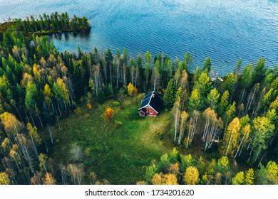Vue aérienne de la cabane en bois rouge ou de la cottage avec sauna dans la forêt printanière au bord du lac en Finlande rurale