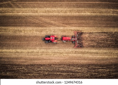 Aerial top view of red tractor seeding plants in the field. Precision agriculture stubble-tillage.