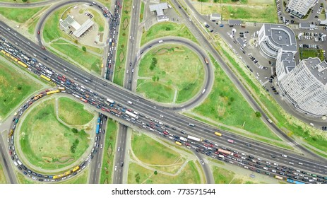 Aerial top view of road junction from above, automobile traffic and jam of many cars, transportation concept, Kiev city skyline, Obolon residential district