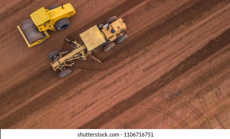 Aerial top view road roller and loader excavator tractor and soil grade car earthmoving at work.