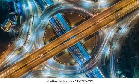 Aerial top view road roundabout intersection in the city at night with vehicle car light movement.