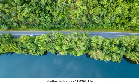 Aerial top view road track with car and river, around the tree and forest, Aerial view of the road through river and forest.