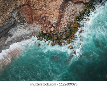 Aerial top view of sea waves hitting rocks on the beach with turquoise sea water. Amazing rock cliff seascape in the Portuguese coastline. Drone shot.