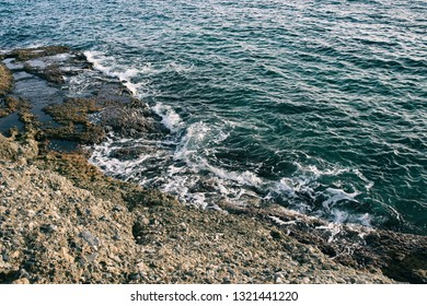 Aerial top view of sea waves hitting rocks on the beach with turquoise sea water. Amazing rock cliff seascape in the coastline. Aerial view of sea waves and fantastic Rocky coast. Mediterranean Sea.