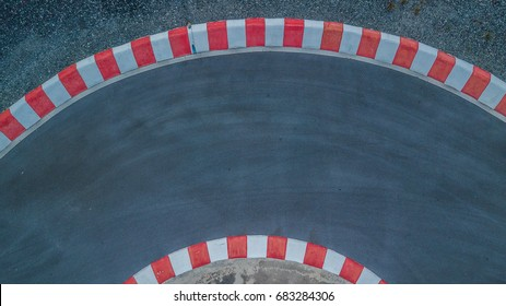 Aerial top view sharp curve asphalt race track with red stripe.