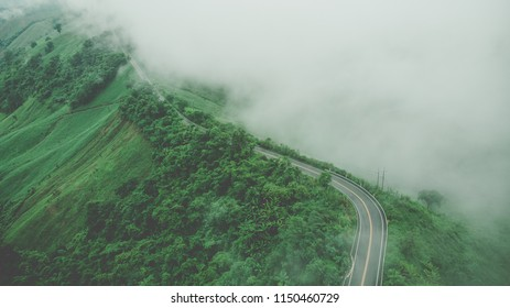 Aerial top view of sky road over top of mountain with fog and green jungle after raining in morning, Pua, Nan, Thailand. The transportation road across mountain. Shot from drone.