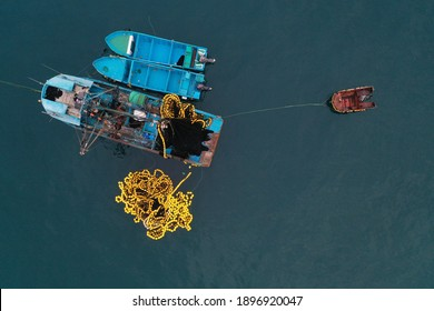Aerial top view of a small blue colored fishing boat with a fishingnet floating alongside