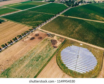 Aerial top view of station with solar batteries in agricultural area near field. Alternative energy production system favorable to nature environment. Innovative biofuels photovoltaic technology