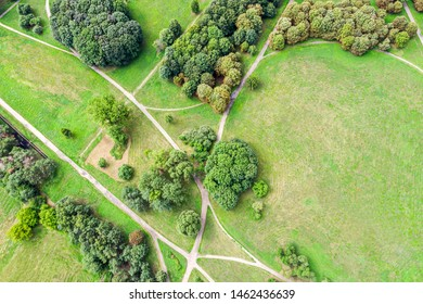 aerial top view of summer park landscape with green trees, lawns and footpath