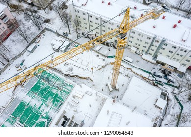 aerial top view of tall tower crane working at construction site in winter. drone photography