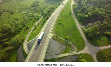 Aerial Top View of White Truck with Cargo Semi Trailer Moving on Road in Direction f Loading Warehouse Area.