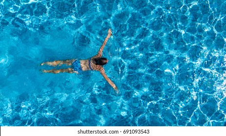 Aerial top view of woman in swimming pool water from above, tropical vacation holaday concept