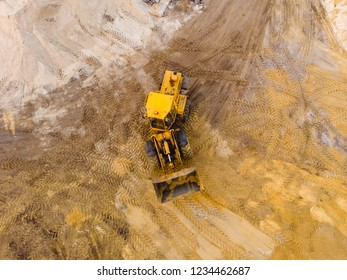 Aerial or top view of yellow excavator or bulldozer works in sand quarry or construction site