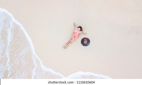Aerial top view young woman in a bikini lying on the sand beach and waves, Young woman sunbathing and relaxing on the white sandy beach, Summer travel concept.