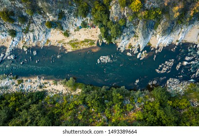 Aerial top-down photo of a blue river in a mountain canyon with green forest and a touristic camp
