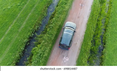Aerial top-down photo of offroad SUV sport utility vehicle driving fast over unpaved gravel road in between two straight canals off-road truck driving fast in straight direction