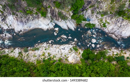 Aerial top-down photo of a river in a mountain canyon with green forest and rocks in the river