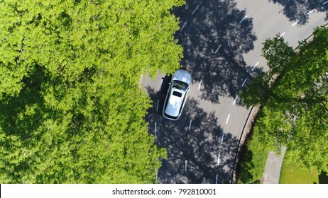 Aerial top-down photo silver grey self driving test car driving through corner simple two lane road with trees left and right at side of road