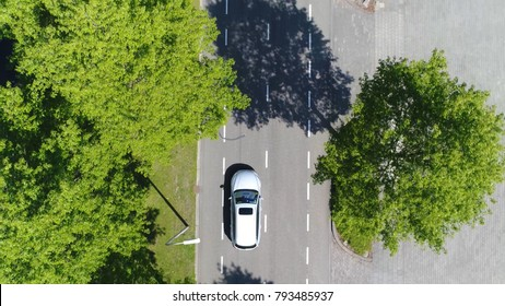 Aerial top-down photo silver grey self driving test car driving over straight road simple two lane road with trees left and right at side of road