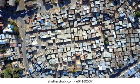 Aerial top-down view high altitude of slum a heavily populated urban informal settlement characterized by substandard housing and squalor poor living conditions streets and rusty metal home roof tops