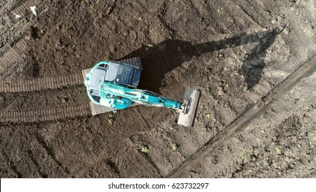 Aerial top-down view of hydraulic excavator driving over brown soil  sand surface heavy construction vehicle on tracks also showing its shadow