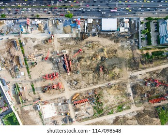 Aerial topdown view of large construction site in urban city. With Many trucks, sand pit, concrete block. Urban construction concept.