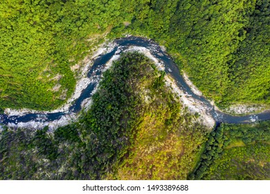 Aerial top-down view of a river crossing mountain range