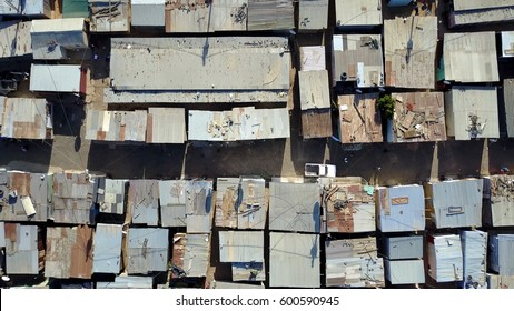 Aerial top-down view of slum low altitude heavily populated urban informal settlement characterized by substandard housing and squalor people walking through streets and rusty metal home roof tops