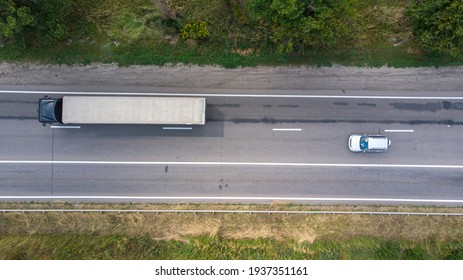 Aerial. Traffic by the rural highway. Sedan car and truck on the motorway. Top view from drone.