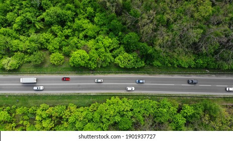 Aerial. Traffic on the intercity highway between the natural parkland. Top view from drone.